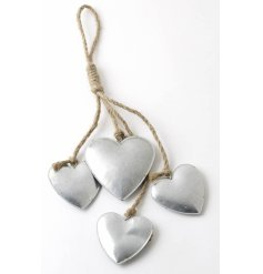 Cluster of uneven sized metal hearts hanging on rustic twine 32cm