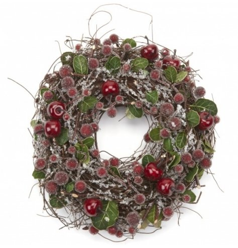 A rustic twig wreath with wispy branches, artificial leaves, frosted red berries and apples.