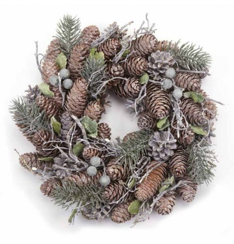 A rustic pinecone wreath with green branches and berries.
