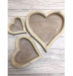 A rustic set of natural wooden trays complete by their heart shape and small sizes