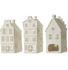 A set of three white porcelain festive house t-light holders.
