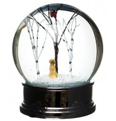 A cute snow globe with a festive winter scene including a golden labrador.