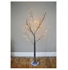 A gorgeous tall standing twig tree featuring warm glowing LED accents and a snowy decal