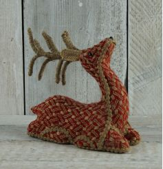 A charming rustic woven reindeer decoration in festive red and cream colours.