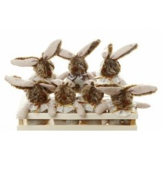 An adorable display of fluffy bunnies in a wooden crate