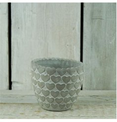 A chic flower pot made from stone with a white wash finish and heart pattern.