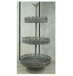 A shabby chic metal stand with decorative bird