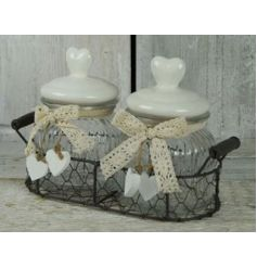 Two glass jars inside a rustic wire basket with heart lids