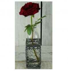Wire basket with decorative glass bottle inside