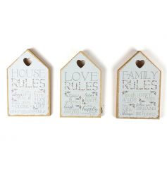 An assortment of three wooden house signs with popular rules text