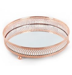 A mirrored candle plate with copper finish