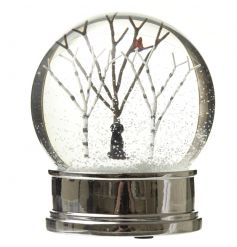 A charming snow globe with a winter scene and black labrador ornament.