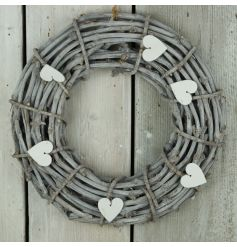 A beautiful wicker wreath with a whitewashed finish and shabby chic wooden heart decorations.
