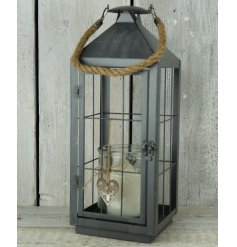 A beautiful dark grey metal lantern with a jute bow and heart featuring a reindeer design.