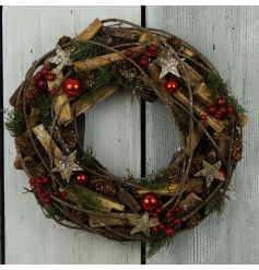 A stunning natural twig wreath decorated with bark stars, red baubles, berries, pinecones and glitter.