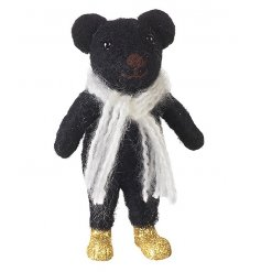 A little black felt bear decoration with winter scarf and gold glitter boots