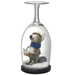 A unique festive decoration. An adorable carol singer bear displayed within a wine glass with snow.