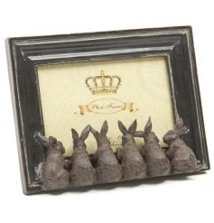 A dark wood effect photo frame with little sitting rabbits
