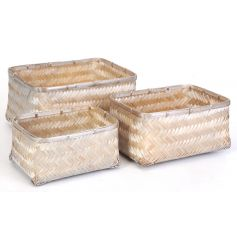 A set of 3 bamboo woven baskets in 3 stackable sizes with a champagne finish.
