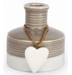 A stylish ceramic vase with a decorative heart ornament.