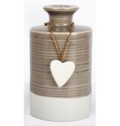 A decorative shabby chic style glazed vase with a hanging heart ornament.