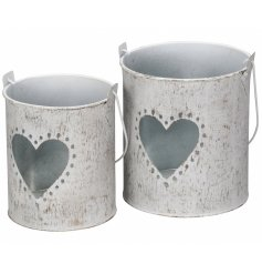 A set of 2 distressed metal lanterns with a heart detail.