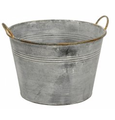An extra large round metal planter featuring a distressed white washed setting and tarnished handles