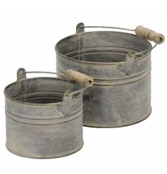 A set of 2 rustic style grey buckets each with wooden handles. Multi-purpose and stylish decorative buckets.