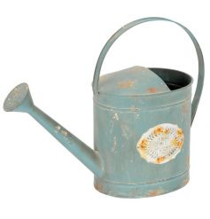 A vintage Parisian style watering can in blue with a metal embossed label and a distressed finish.