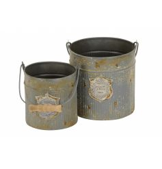 Stay on trend with this set of 2 antique effect ribbed buckets in grey. Complete with emblem and wooden handle.