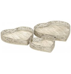 A set of 3 metal heart shaped trays each with a decorative pattern.