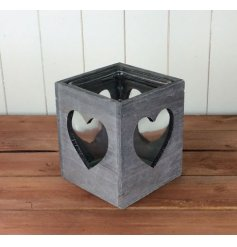 A rustic wooden candle holder with heart cut out design.