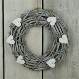 A charming wicker wreath with a grey washed finish and white wooden hearts.