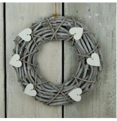 A shabby chic style wicker wreath with a grey washed finish and white heart decorations.