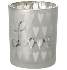 A silver glass t-light holder with a decorative heart pattern with love slogan.