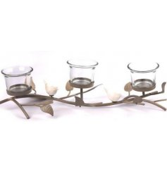 A unique sculptural t-light holder with three candle holders and a decorative bird and leaf motif.
