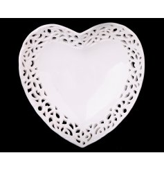 A shabby chic style heart shaped trinket dish with a lace design trim.