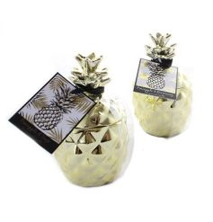 A tropical inspired ceramic pineapple pot filled with a sweetly scented wax centre