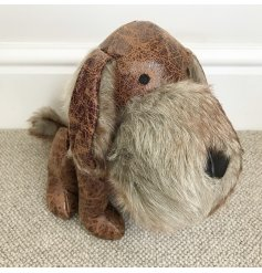 A charming little faux leather sitting dog doorstop, complete with a faux fur snout and distressed look