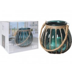 A decorative glass lantern with chunky jute rope. Includes an LED candle and pebbles.
