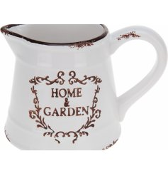 A shabby chic style ceramic jug with a distressed finish and Home & Garden slogan.