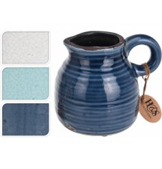 A mix of 3 ceramic jugs in blue and cream colours. A glazed jug with a distressed finish.