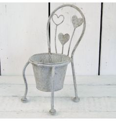 A stylishly distressed grey metal garden chair with planter placement