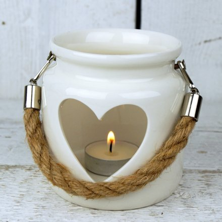 A small decorative porcelain lantern with a heart cut decal and rope handle