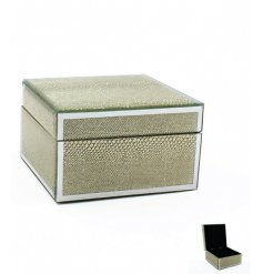 A glamorous glass trinket box with a gold snakeskin design and black lining.