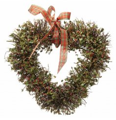 A traditional themed hanging heart shaped wreath, finished with scattered berries and holly