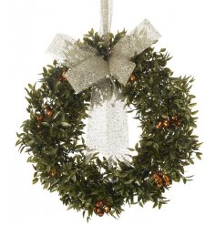 A large traditional wreath with bronze berries and sparkly gold hanging ribbon