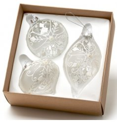 A set of 3 glass baubles with a white glitter lace design.