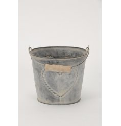 A rustic style grey metal bucket with a wooden handle and heart design. Ideal for use as a hamper and planter!