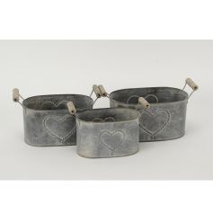 A set of 3 metal oval shaped planters each with a heart design and twin handles.